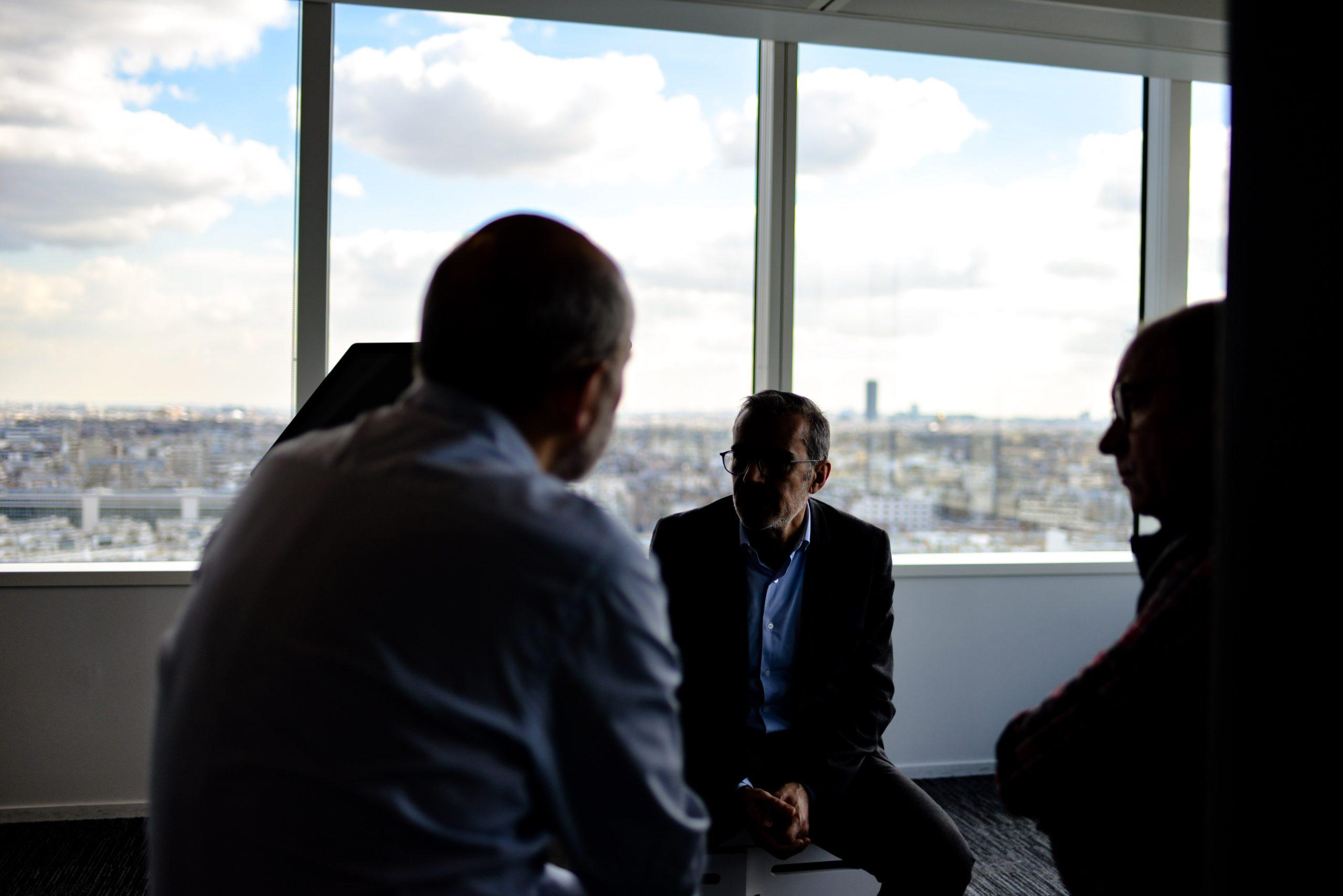 Unidentifizierbare Personen in Büro vor Ausblick auf Großstadt